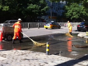 Two men sweeping the left over flood water into a sewer drain.