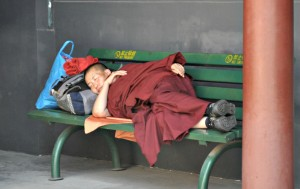 In the middle of the hustle and bustle, a monk finds time to sleep.