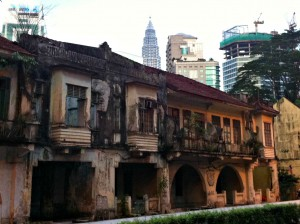 One of the Petronas Twin Towers stands behind a row of houses that are falling apart.