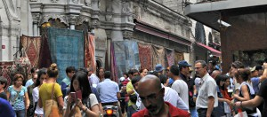 People mingling and rugs hung on the wall outside The Grand Bazaar.