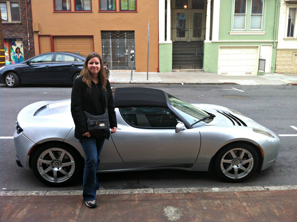 Jill standing beside the All-Electric Tesla Roadster.